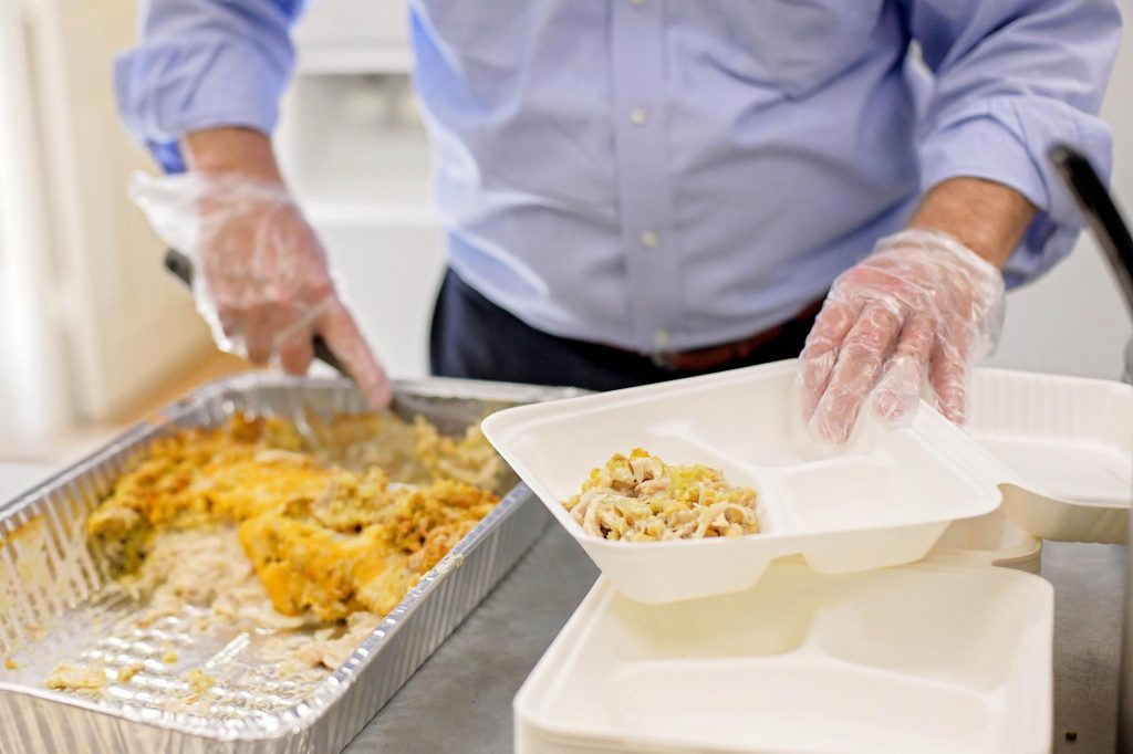 Volunteer in blue dress shirt serving food in takeout tray
